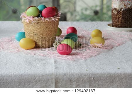 dyed eggs for Easter in the basket and cake on the table