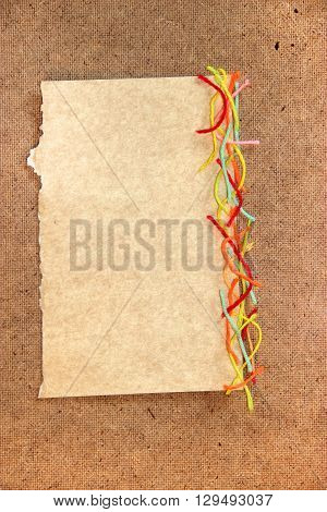 piece of cardboard bright colorful wool thread piece of paper element laid out on cardboard with a place for accommodation on background for scrapbook object