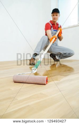 Lacquering wood floors. Use roller for coating floors.
