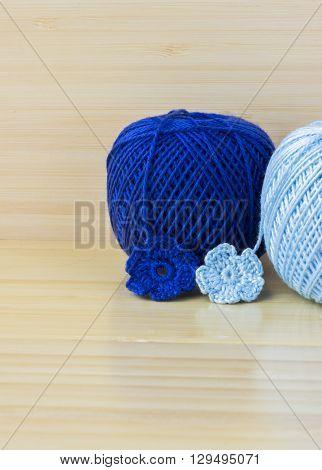 Blue balls of cotton yarn for knitting crochet. Crochet flowers on bamboo background