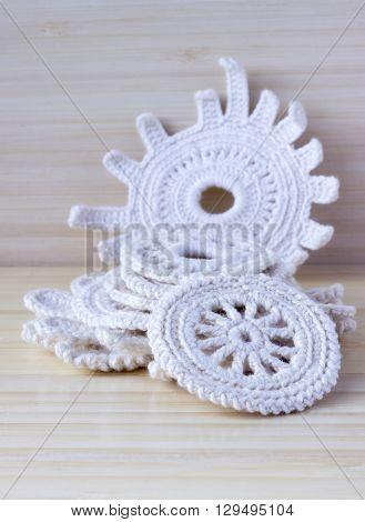 Crochet doilies crochet pattern coasters on bamboo wooden background. Irish crochet elements