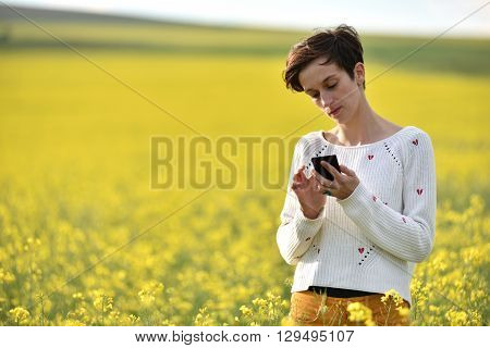 Young Hipster Girl Texting A Message In The Middle Of A Canola Field