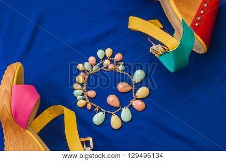 Summer sandals and bracelet on a blue background