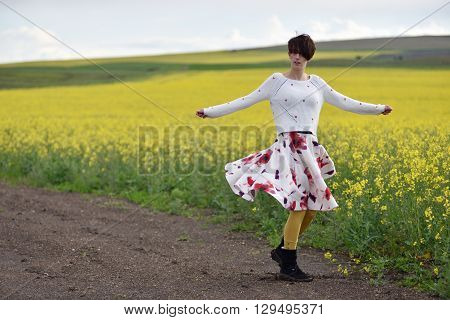 Sexy Woman In Skirt Dancing Near A Canola Field