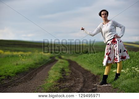 Sexy Young Woman In Dress Hitchhiking Near A Countryside Road