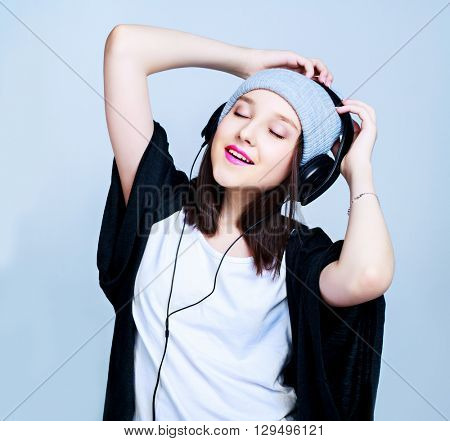 happy teenage girl with earphones, isolated against blue studio background