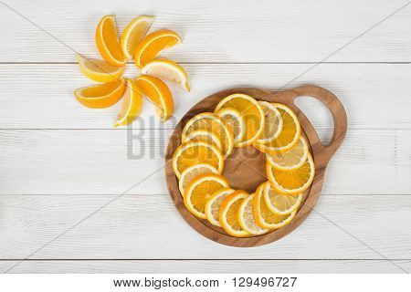 Orange slices are well decorated on a cutting board. Top view composition. Food decoration. Boosting immune system. Helps prevent ageing of skin. Protects your vision.