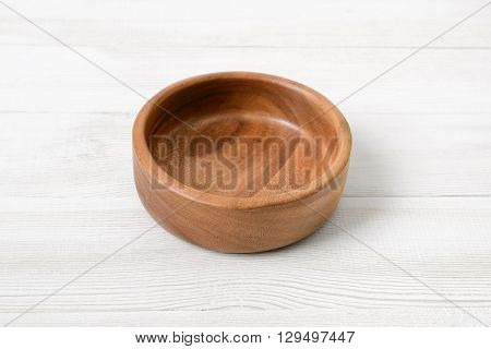 Wooden bowl. on white wooden surface. Wooden Tableware. Environmentally friendly goods. Durable material. Naturally beautiful goods. Strength material. Safe to use.