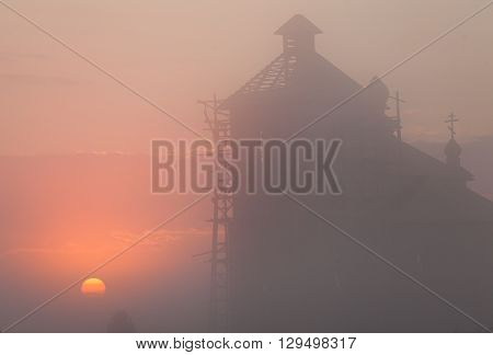 A silhouette of a church steeple at sunset