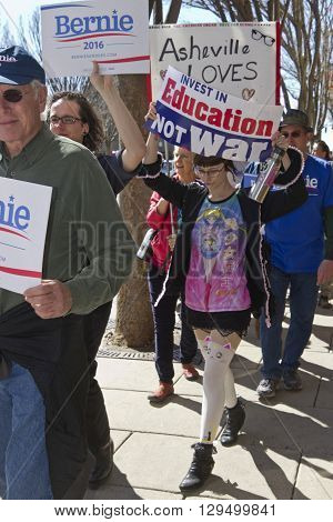 Asheville, North Carolina, USA - February 28, 2016: Crowd of colorful Bernie Sanders supporters march down a street corner holding signs during a political rally on February 28 2016 in downtown Asheville, NC