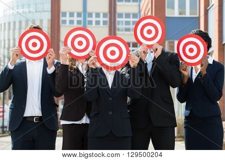 Group Of Professional Businesspeople Hiding Face With Red Dartboard