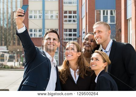 Group Of Businesspeople Taking Selfie With Mobile Phone