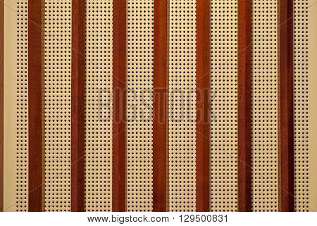 The perforated plate is beige and brown wooden slats to use as a background.