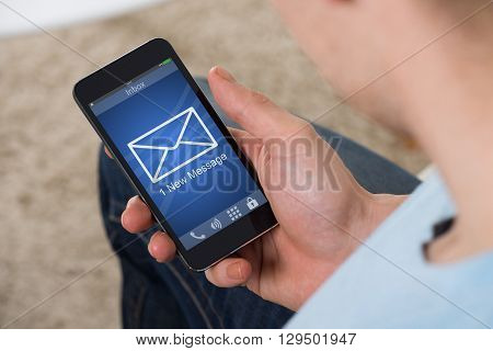 Close-up Of A Man Looking At New Message Received On His Mobile Phone
