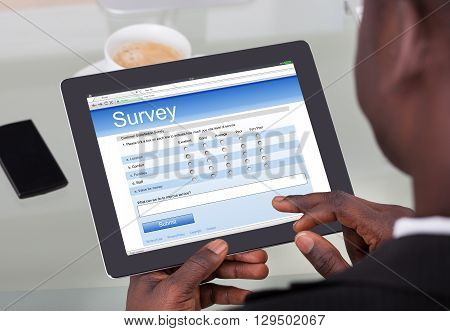 Close-up Of A Businessperson Filling Survey Form On His Digital Tablet At Office