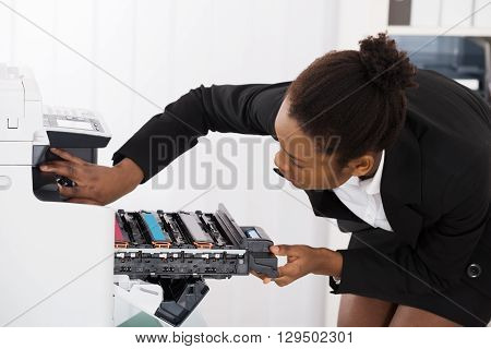 Young Businesswoman Fixing Photocopy Machine In Office
