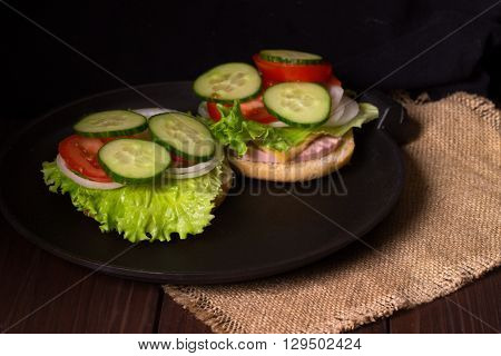 Sandwich with salad and other vegetables on a wooden table and a sacking. On a half of a roll the lettuce leaf onions rings a tomato piece sausage lies. Close up small depth of sharpness