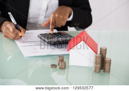 Businesswoman Calculating Invoice With House Model And Stack Of Coins On Desk