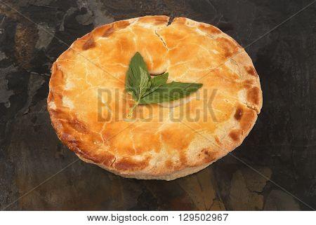 Freshly baked pie arranged against grey slate backround