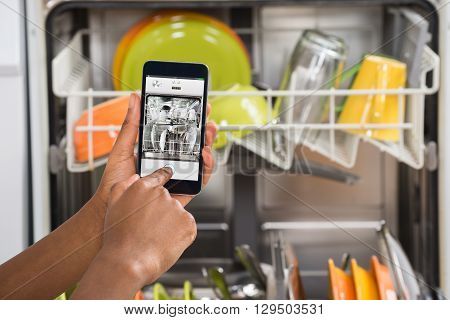 Close-up Of Person Hands Operating Dishwasher With Mobile Phone