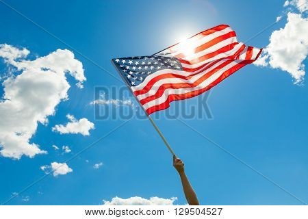 USA flag in hand with white clouds and blue sky on background