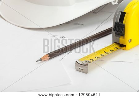 Close Up Shot Of White Construction Helmet With Pencil And Measure Tape