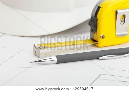Close Up Studio Shot Of White Construction Helmet With Pencil And Measure Tape