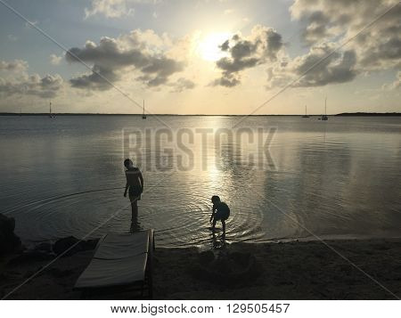 A silhouette of two boys playing in the water with the sun setting in the background.