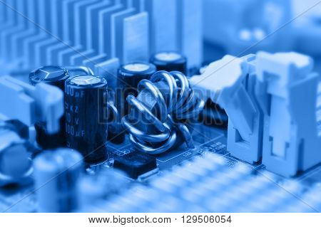 Closeup of electronic circuit board with inductor coil and capacitor.