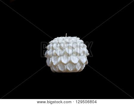 White wax candle of round shape with decorative petals