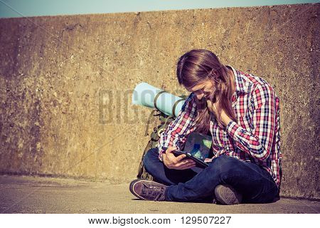 Man tourist backpacker relaxing outdoor sitting by grunge wall using tablet. Internet tourism active lifestyle. Young hipster guy tramping