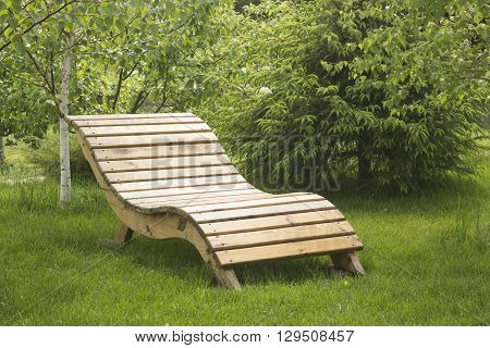 lacquered wooden garden yelow bench on the lawn