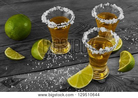 Three shots of gold tequila with lime and salt on the black background. Vintage toned photo. Tequila shot. Gold Mexican tequila. Tequila
