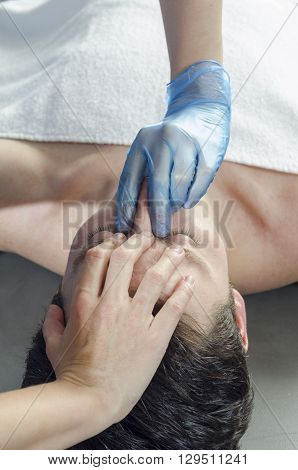 Physiotheraphist doing a sinus massage theraphy to male patient.