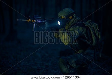 Military Night Operation. Soldier with Assault Rifle and Flashlights at Night.