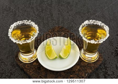 Two gold tequila shots with lime. Tequila shot. Gold Mexican tequila. Tequila