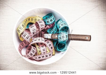Many Measuring Tapes In Bowl On Table
