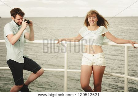 Young Couple In Love Is Taking Photos On Sea Pier.