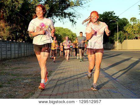 Rustenburg Marathon Club Rainbow Run - NOVEMBER 25: Two Chearful running young girls covered with powder paint at colour run on November 25 2015 Rustenburg South Africa.