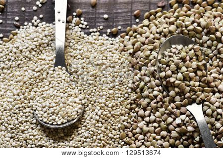 high-angle shot of some spoons with different edible seeds such as buckwheat or quinoa, on a rustic wooden surface