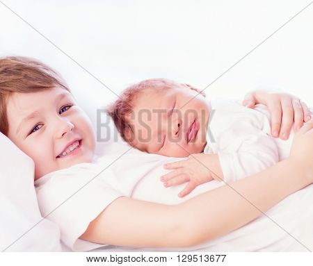 Portrait Of Cute Happy Siblings. Young Boy Holding His Infant Brother