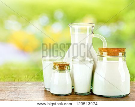 Pitcher, jars and glasses of milk on wooden table against blurred green background