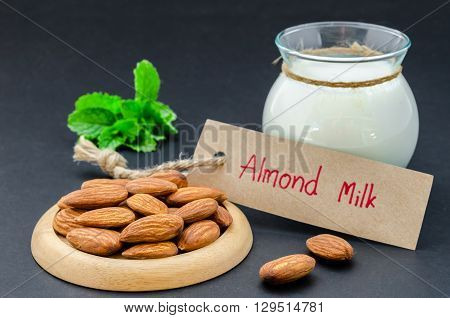 Almond seeds with almond milk in glass cup on black background.