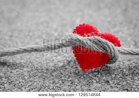 Red heart with a bundle rope on a black and white color wooden board