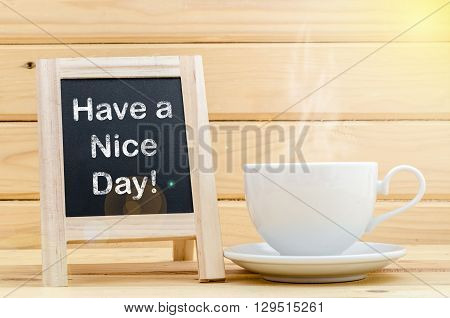 Have a nice day word on chalkboard and coffee in white cup with smoke. Day light.