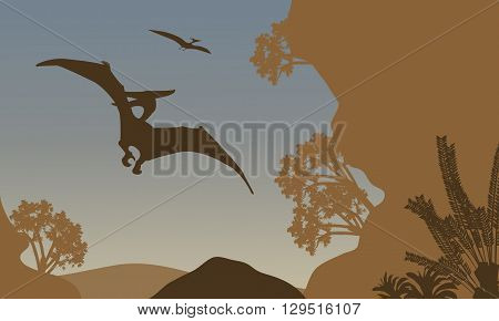 Silhouette of pterodactyl flying in forest at the afternoon