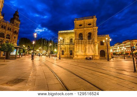Tram tracks, historic buildings and the streets of the center of Seville illuminated by night. Seville town, Andalusia, Spain.