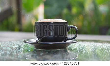 Hot cappuccino coffee cup on glass table in garden with dewdrop foreground