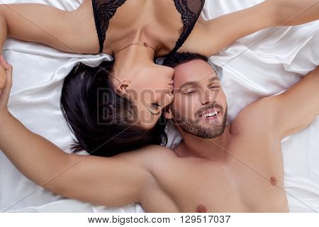Sexy woman kissing man in head and he pretty smiling
