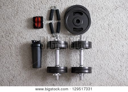 Dumbbells with expander and shaker on the carpet